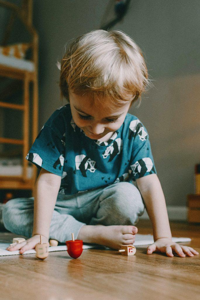Boy spinning wooden spinner