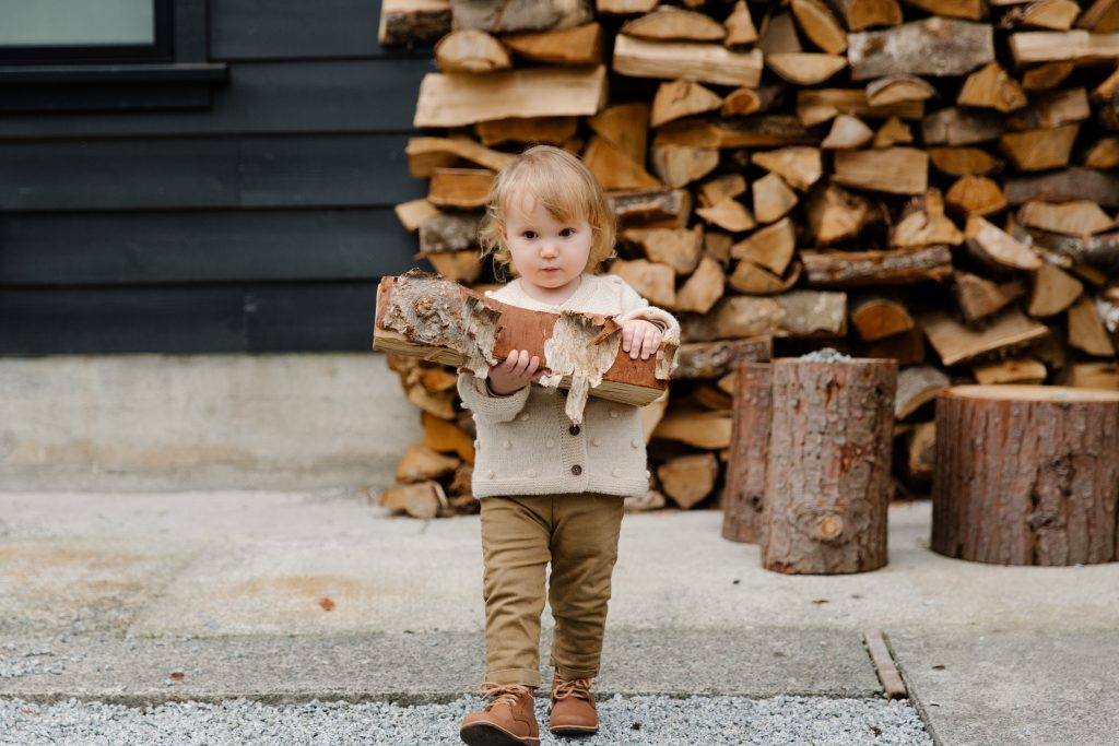 Child carrying wooden logs